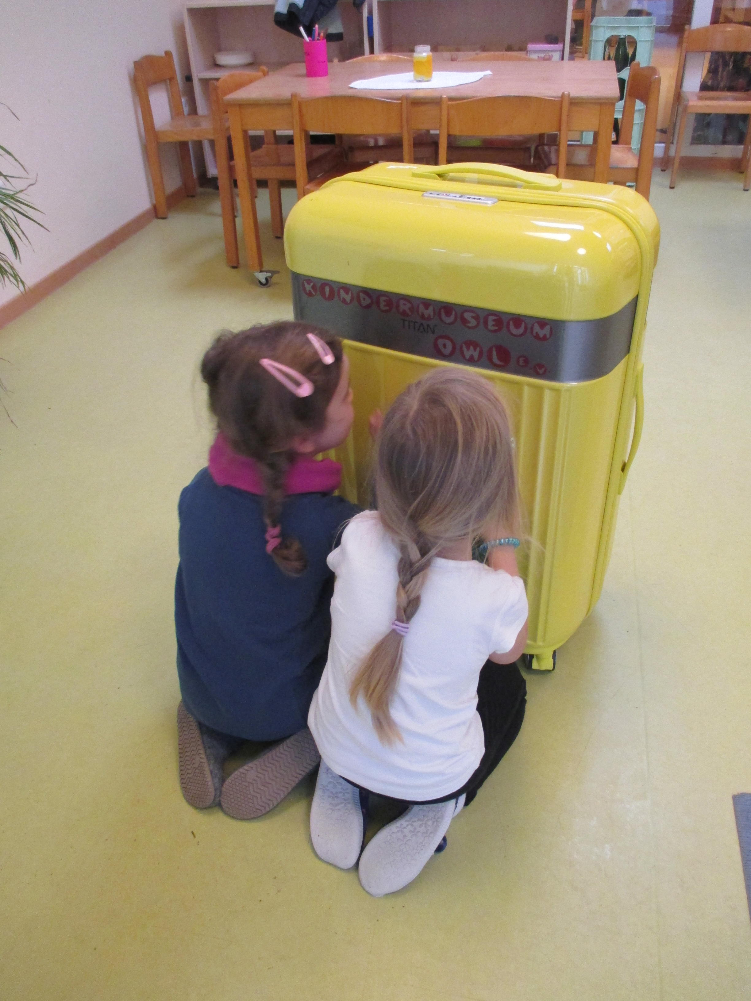 Kinder knien vor Demokratiekoffer.